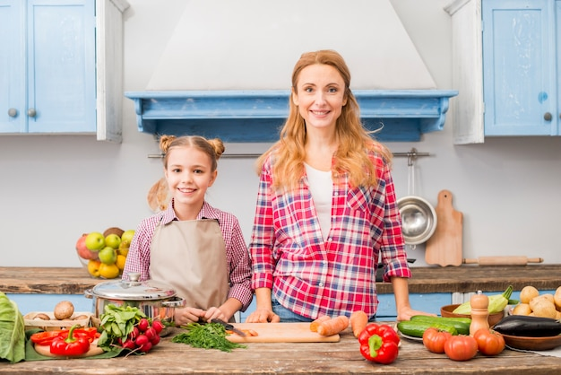 Portrait of a smiling mother and her daughter standing in front of table with vegetables Free Photo