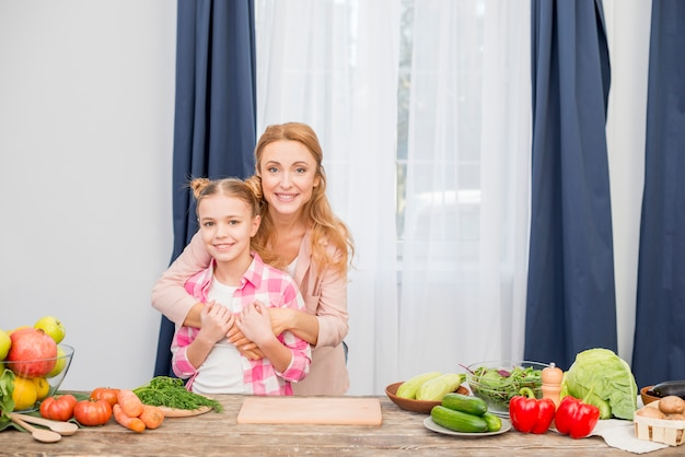 Portrait of a smiling mother and her daughter standing behind the wooden table looking at camera Free Photo