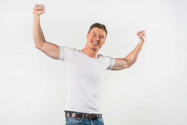 Portrait of a smiling muscular man clenching her fist against white backdrop Free Photo