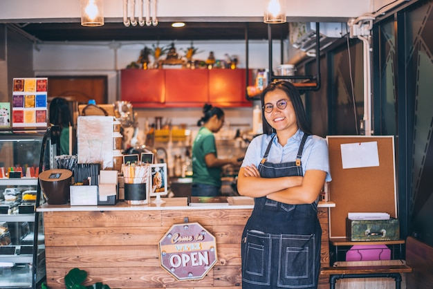Portrait of smiling owner standing at coffee shop, small family business. portrait of smiling owner standing at front counter bar Premium Photo