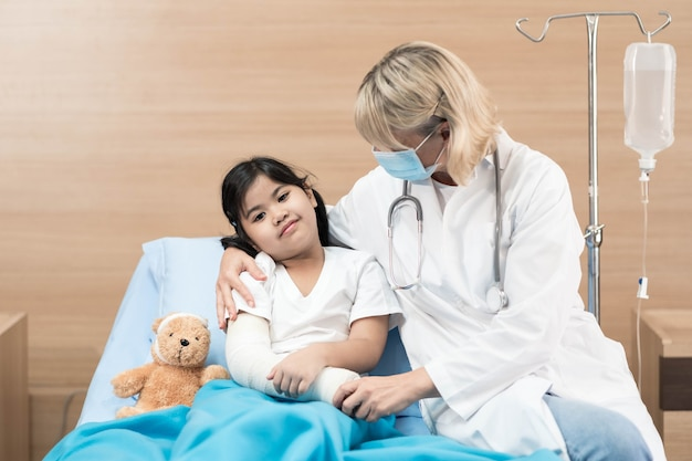 Portrait of smiling pediatrician and little patient on bed Premium Photo