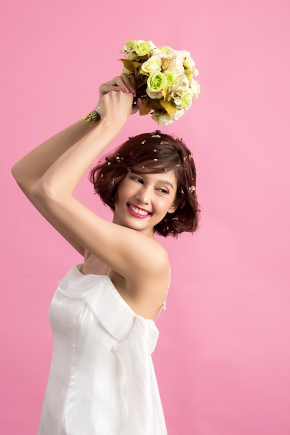 Portrait of a smiling playful cute woman holding flowers isolated on pink Free Photo
