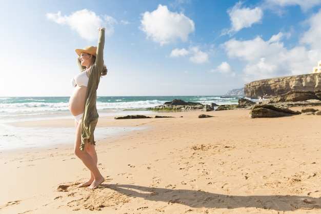 Portrait of smiling pregnant woman stretching arm Free Photo
