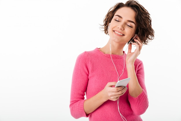 Portrait of a smiling pretty girl listening to music Free Photo
