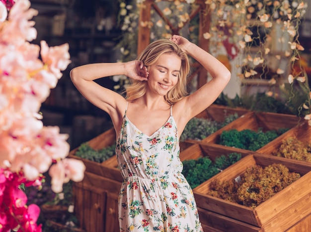 Portrait of a smiling pretty young woman relaxing in the florist shop Free Photo