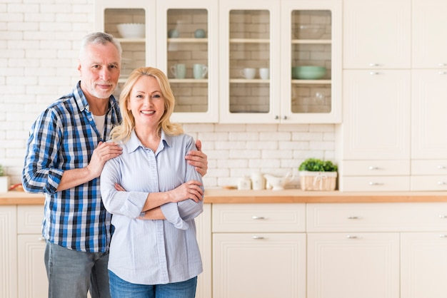 Portrait of a smiling senior couple standing in the kitchen looking at camera Free Photo