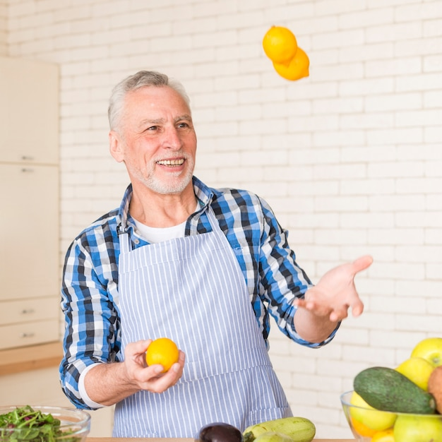 Portrait of a smiling senior man juggling whole lemons while preparing the kitchen Free Photo