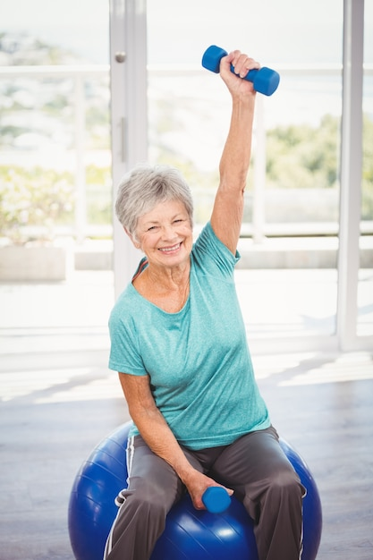 Portrait of smiling senior woman holding dumbbell Premium Photo