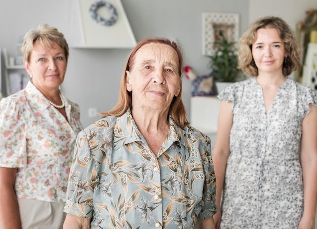 Portrait of smiling senior woman standing wither her daughter and grand daughter Free Photo