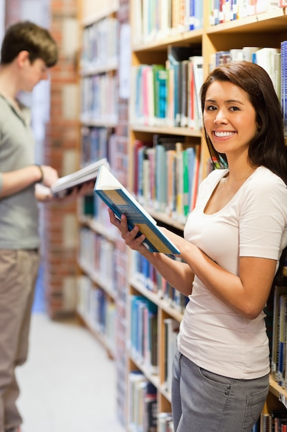 Portrait of a smiling student while holding a book Premium Photo