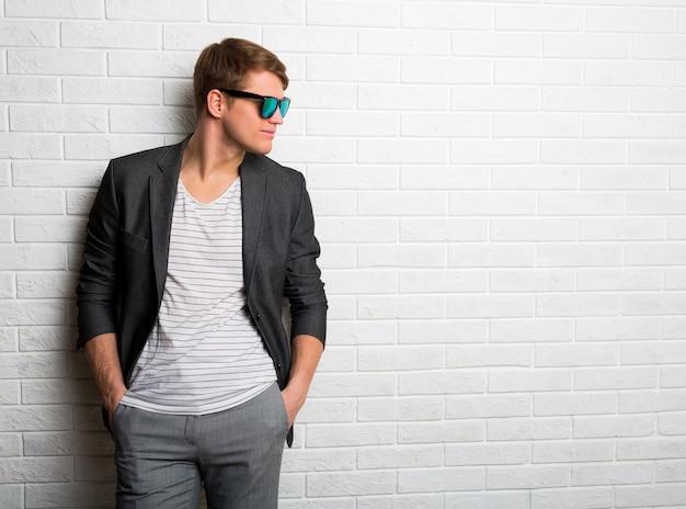 Ritratto di uomo elegante sorridente in occhiali da sole in piedi contro il muro di mattoni in ufficio moderno. Foto Gratuite