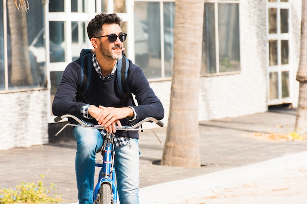 Portrait of smiling stylish man with his backpack sitting on his bicycle looking away Free Photo