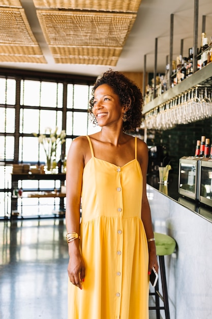 Portrait of smiling stylish young woman standing in the restaurant Free Photo