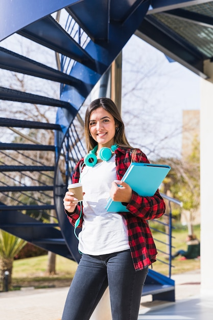 Portrait of smiling teenage female student holding books and takeaway coffee cup looking to camera Free Photo