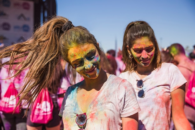 Portrait of a smiling two female friend covered their face with holi color Free Photo