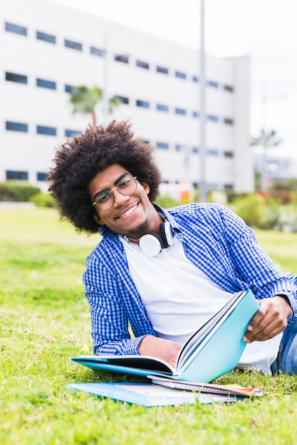 Portrait of smiling university male student holding books in hand lying on campus ground Free Photo
