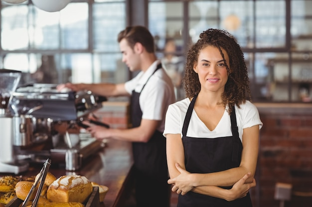 Portrait of smiling waitress with arms crossed in front of colleague at coffee shop Premium Photo