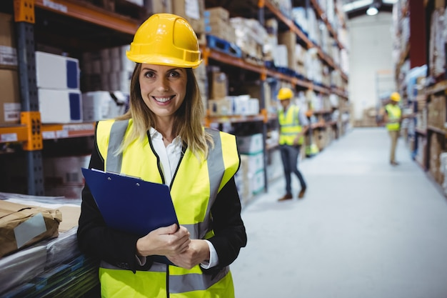 Portrait of smiling warehouse manager holding clipboard Premium Photo