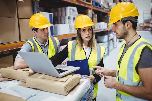 Portrait of smiling warehouse managers using laptop Premium Photo