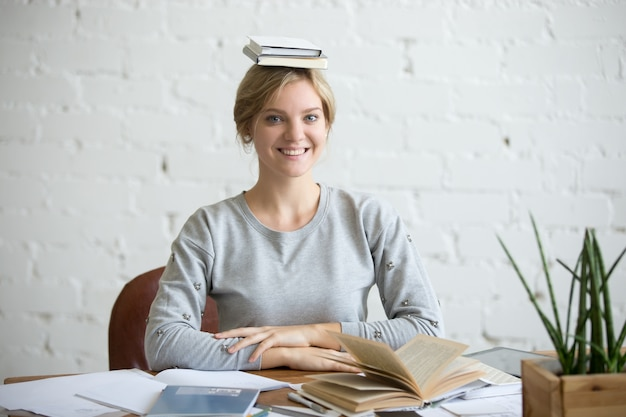 Portrait of smiling woman at desk, books on her head Free Photo