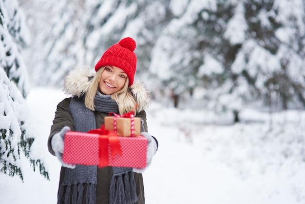 Ritratto di donna sorridente che dà due regali di natale Foto Gratuite