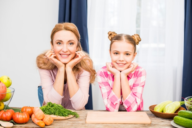 Portrait of a smiling woman and her mother leaning on table with their head on hand looking at camera Free Photo