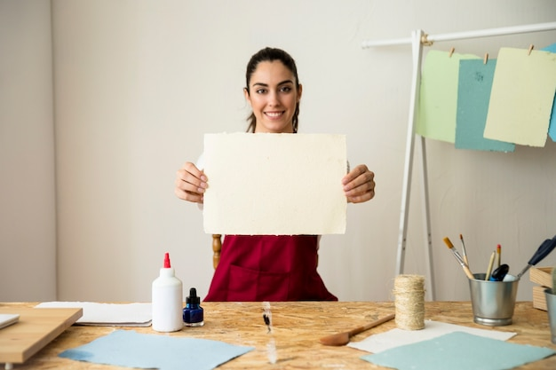 Portrait of a smiling woman holding handmade paper Free Photo