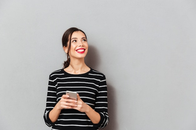 Portrait of a smiling woman holding mobile phone Free Photo