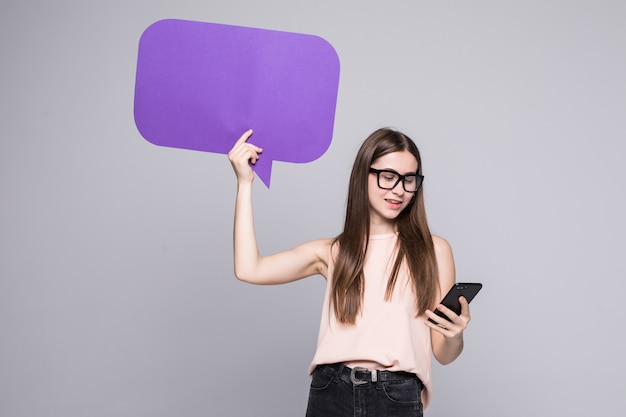 Portrait of a smiling woman showing blank speech bubble and holding mobile phone isolated over gray wall Free Photo