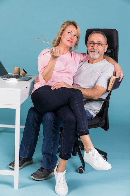 Free Photo Portrait Of A Smiling Woman Sitting On Mans Lap While Sitting On Chair