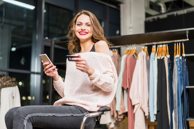 Portrait of a smiling woman sitting in store holding credit card and mobile phone in hand Free Photo