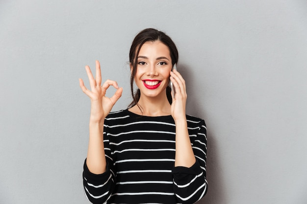Portrait of a smiling woman talking on mobile phone Free Photo