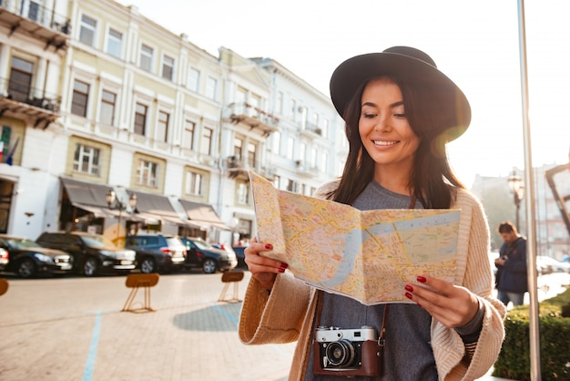 Portrait of a smiling woman tourist holding city map Free Photo