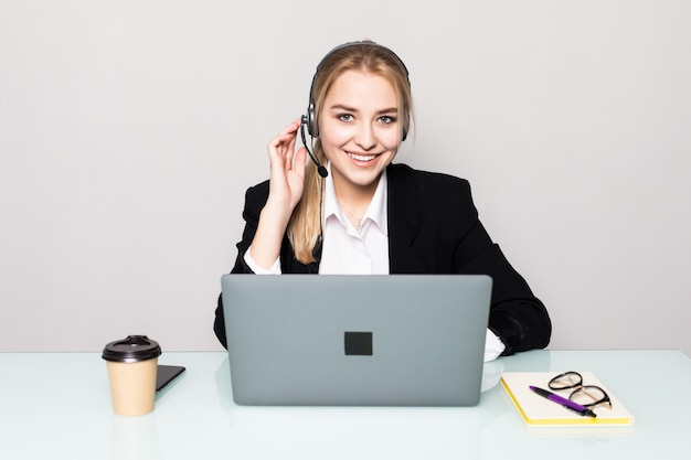 Portrait of smiling woman with laptop helpline operator with headphones at office Free Photo