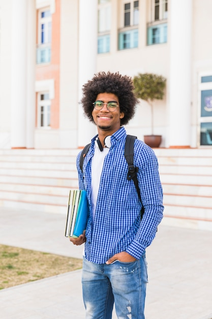 Portrait of smiling young afro male student holding books in hand standing against university building Free Photo