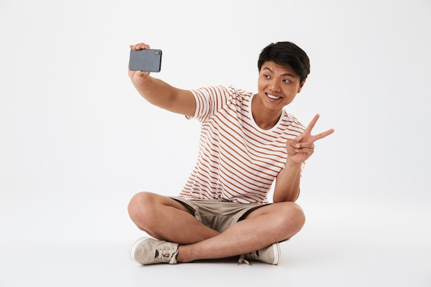 Portrait of a smiling young asian man taking a selfie Premium Photo