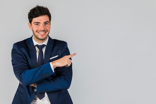 Portrait of a smiling young businessman pointing his finger against grey backdrop Free Photo