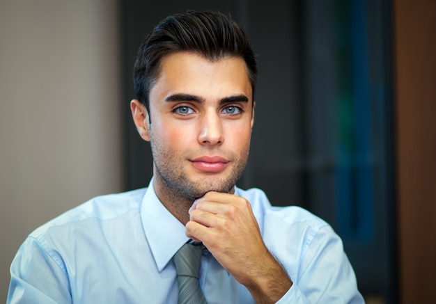 Portrait of a smiling young businessman sitting in his office Premium Photo