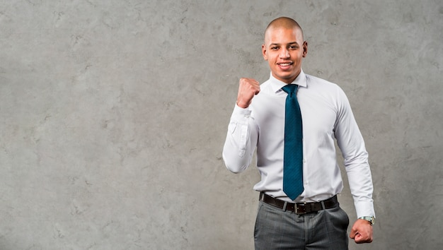 Portrait of a smiling young businessman standing against grey wall clenching his fist Free Photo