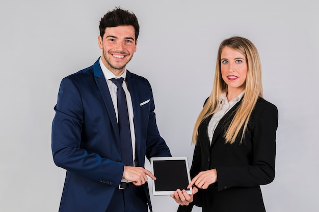 Portrait of a smiling young businesswoman and businessman pointing digital tablet against grey backdrop Free Photo