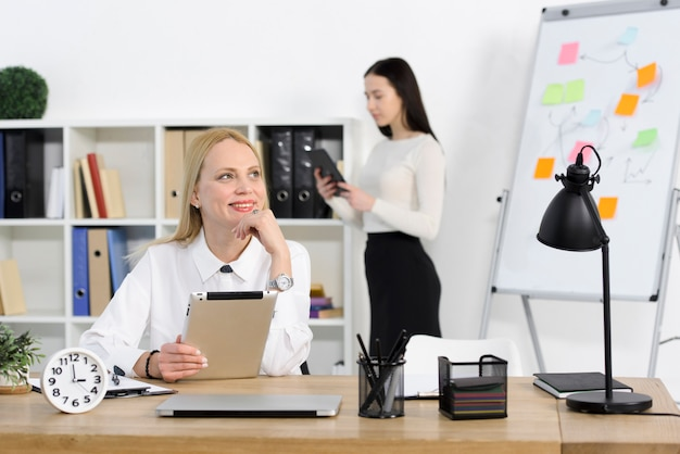 Portrait of a smiling young businesswoman holding digital tablet looking away with her colleague standing at background Free Photo