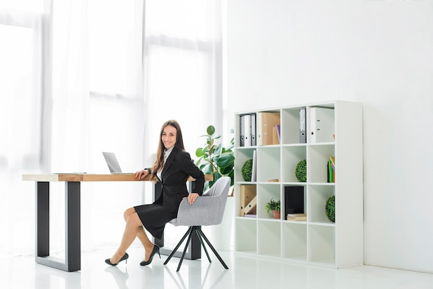 Portrait of a smiling young businesswoman sitting on chair looking at camera Free Photo