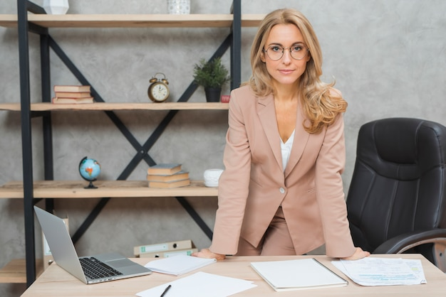 Portrait of a smiling young businesswoman standing at workplace in the office Free Photo