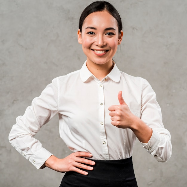 Portrait of a smiling young businesswoman with hand on her hips showing thumb up sign Free Photo