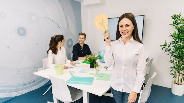 Portrait of a smiling young businesswoman with light bulb icon standing in office Free Photo