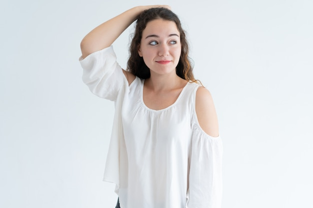 Portrait of smiling young caucasian woman scratching head Free Photo