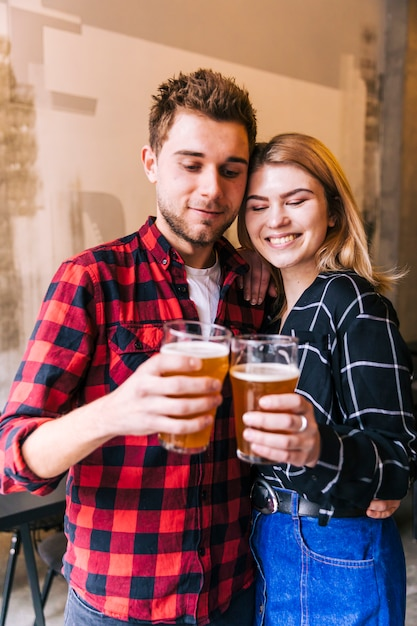Portrait of a smiling young couple cheering the glasses of beer Free Photo