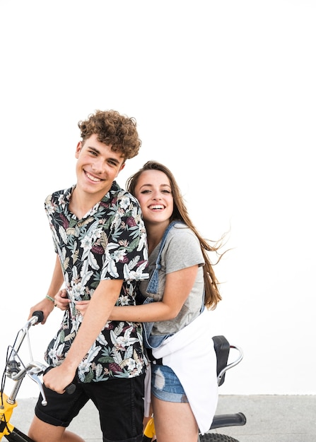 Portrait of smiling young couple enjoying the bicycle ride Free Photo
