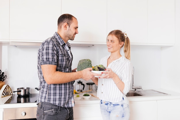 Portrait of a smiling young couple holding bowl of raw