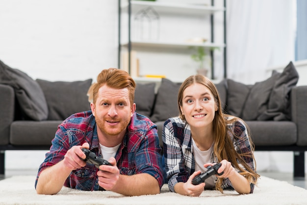 Portrait of smiling young couple lying on carpet playing the video game Free Photo